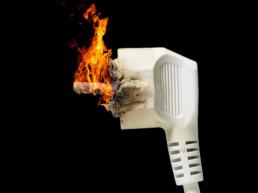 Ein brennender Stecker vor schwarzem Hintergrund